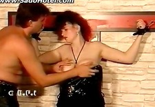Tied slave gets her big tits spanked by master in a dungeon