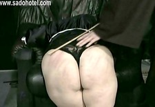 Naughty nun with her skirt up is kneeling for master priest and got spanked with a wooden stick on her well formed ass