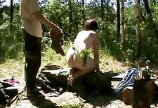 Ritualistic spanking performed by a couple on a log in the woods