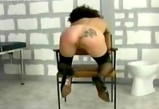 Handcuffed slave bend over a chair is spanked on her well formed ass by a police officer