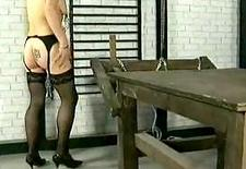 Slave with tiny tits walking around with large metal clamps on her nipples and pussy and master spanks her